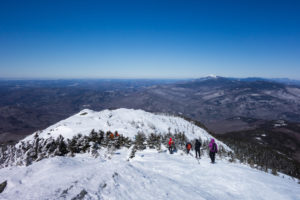 hikers traverse snowy summit with blue sky in background