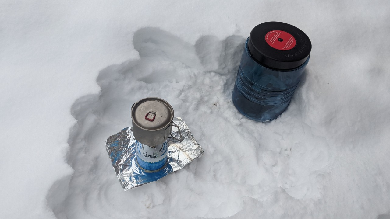 Cooking system and bear canister in the snow for winter camping.